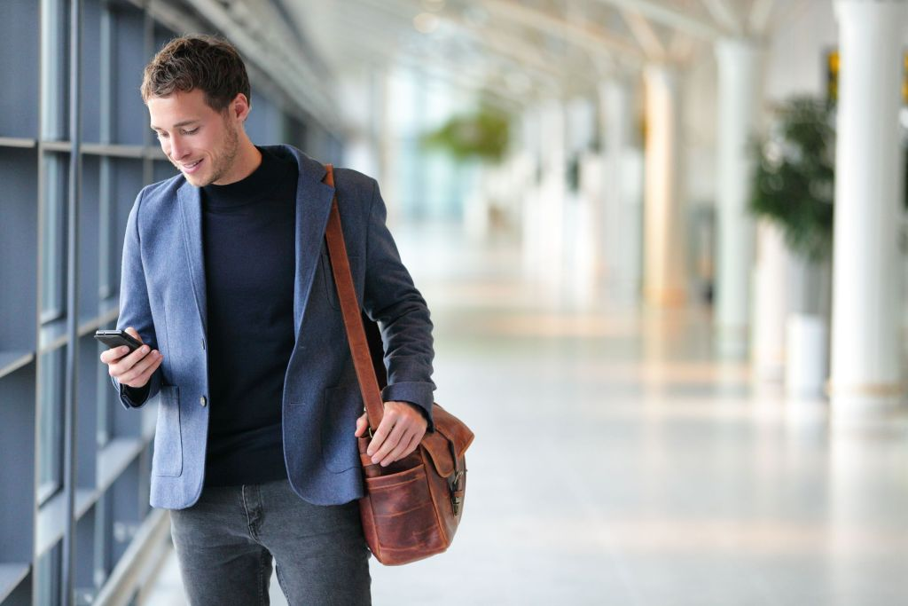 65498953 - business man using mobile phone app in airport. young business professional man texting smartphone walking inside office building or airport terminal. handsome man wearing stylish suit jacket indoors.